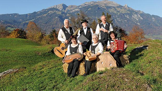 Die Volksmusik-Formation sitzt mitten auf einer Wiese.