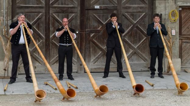 Vier Alphornisten mit ihren Instrumenten vor alter Stalltüre.