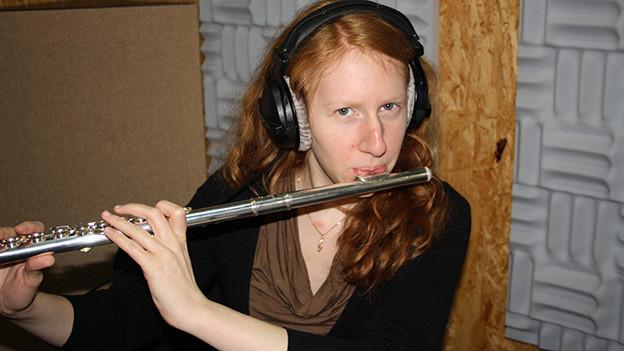 Eine junge Querflötistin mit langen rötlichen Haaren.