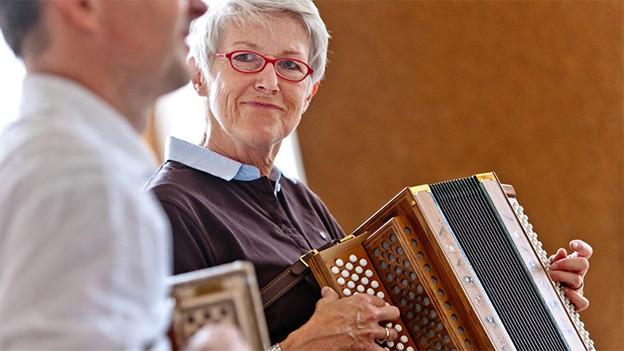 Eine ältere Frau und ein Mann spielen Schwyzerörgeli.