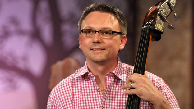 Ein dunkelhaariger Musiker mit Brille spielt Kontrabass.
