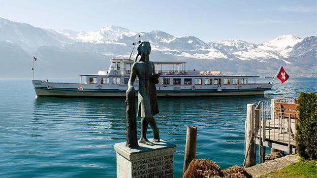 Eine Bronzestatue am Ufer eines Sees.