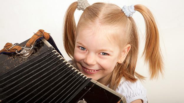 Ein lachendes kleine Mädchen mit blonden Haaren hinter einem Akkordeon.