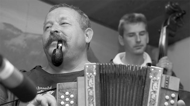Ein Mann mit einer Tabakpfeife spielt Schwyzerörgeli