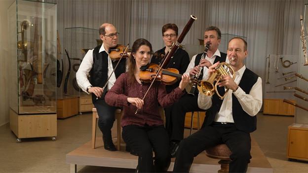 Drei Musiker und zwei Musikerinnen spielen Geige, Klarinette, Posaune und Fagott.