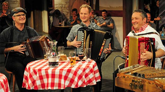 Drei Volksmusikanten in einer Fernsehsendung.