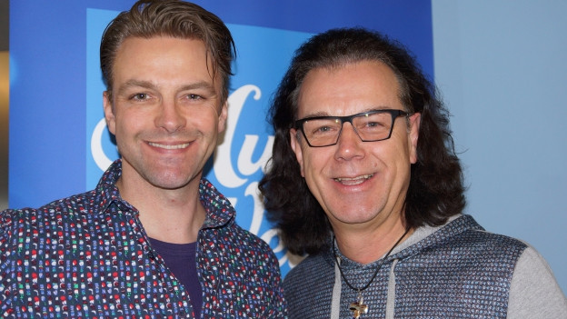 Zwei Männer vor SRF Musikwelle-Logo.