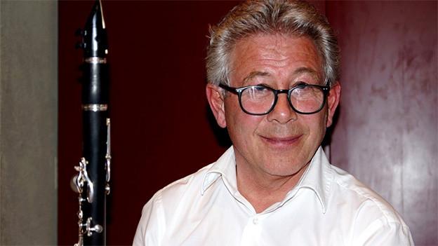 Ein Klarinettist mit grauen Haaren und schwarzer, runder Brille.
