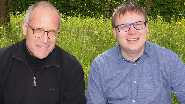 Zwei Männer sitzen auf einer Mauer am Rand einer Wiese.