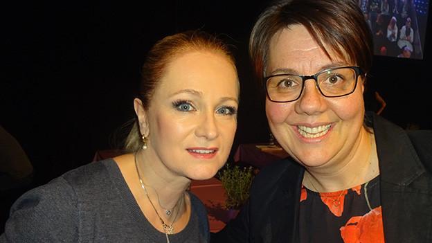Selfie von zwei Frauen vor einer Fernsehkulisse.