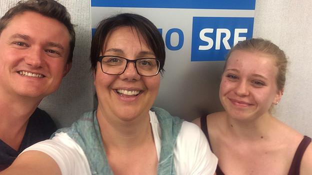 Ein Mann und zwei Frauen machen einen Selfie.