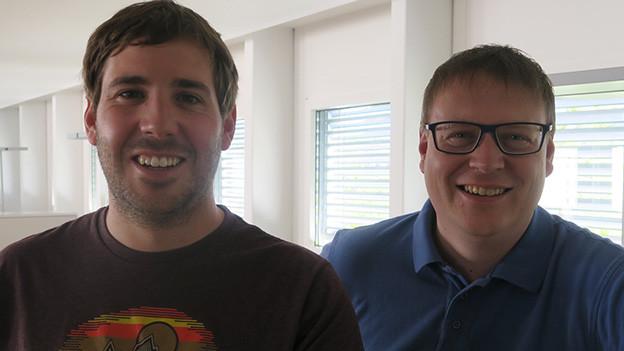 Zwei Männer an einer Theke in einem grossen Büro.