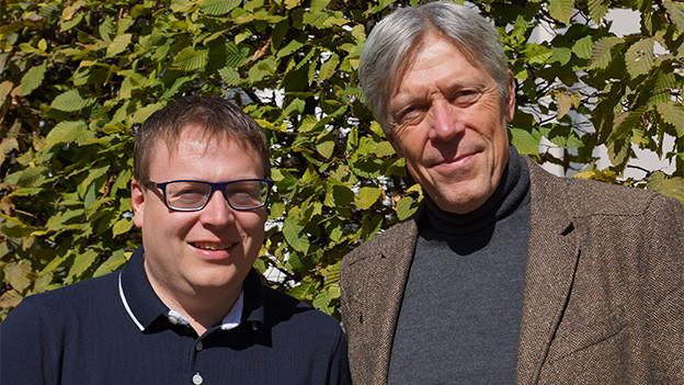 Zwei Männer vor einer grünen Hecke.