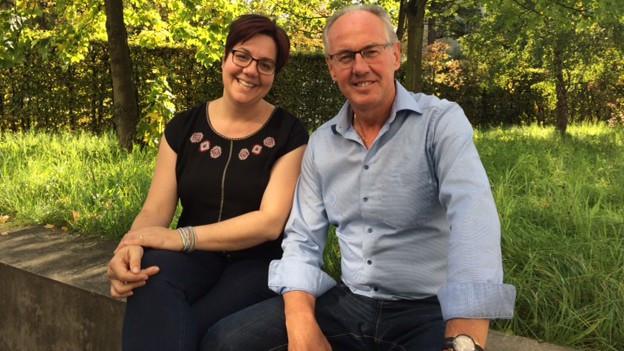 Frau und Mann sitzen auf Steinbank. Im Hintergrund Gestrüpp.