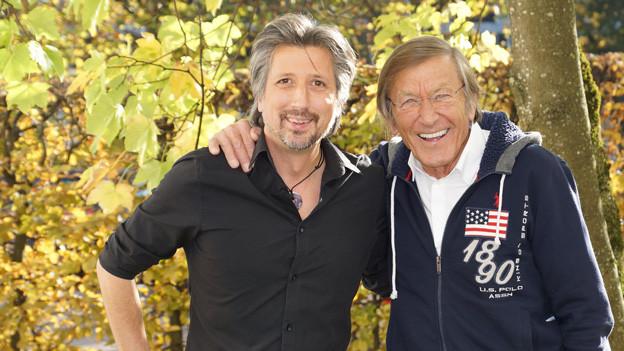 Zwei Männer vor Herbstbaum.