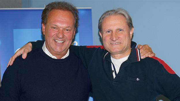 Porträt zweier Männer, die in die Kamera lachen.