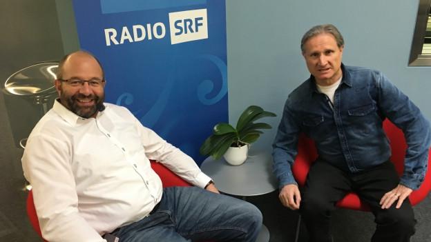 Zwei Männer auf roten Stühlen vor SRF Musikwelle Plakaten.