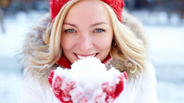 Junge Frau pustet in ihre mit Schnee gefüllten Handschuhe und erzeugt eine Schneewolke.
