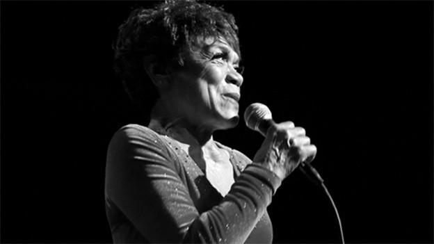 Eine dunkelhäutige Sängerin mit Mikrofon.