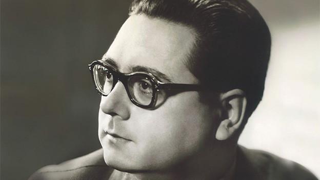 Schwarz-Weiss-Fotografie mit dem Porträt eines dunkelhaarigen Mannes.