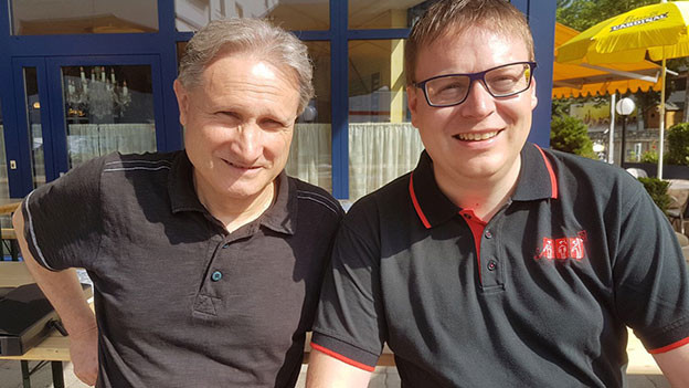 Zwei Männer blinzeln in die strahlende Sonne.