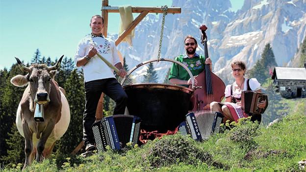 Eine Volksmusikformation mit Kuh auf einer Alp.