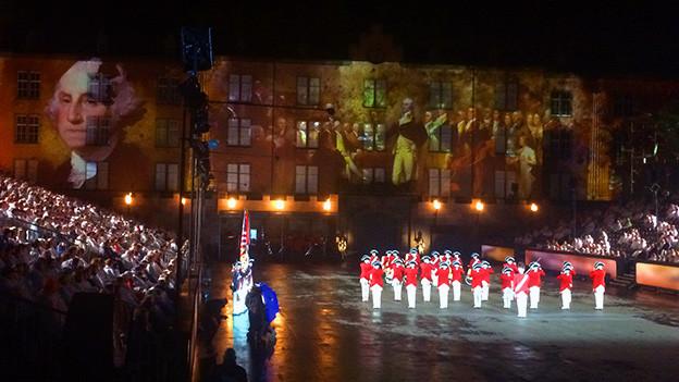 Eine Militärmusikformation in einer Arena vor voll besetzten Zuschauerrängen.
