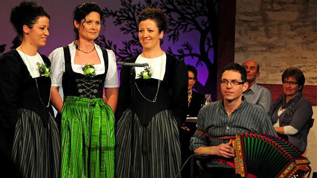 Drei Trachtenfrauen im Fernsehstudio.