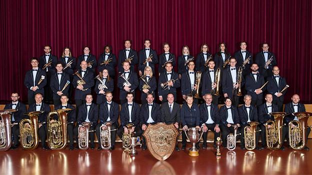Gruppenbild mit vielen Blasmusikantinnen und Blasmusikanten.