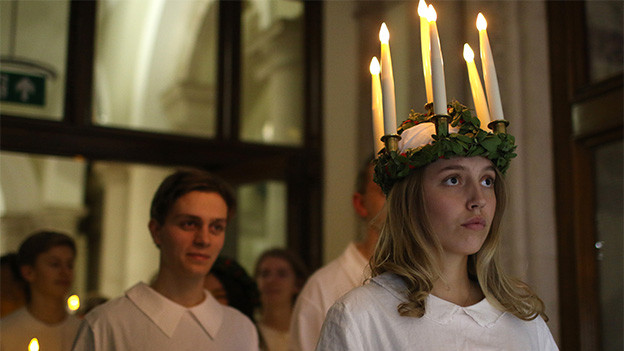 Eine junge blondhaarige Frau trägt ein weisses Kleid und auf dem Kopf einen Kranz mit Kerzen.