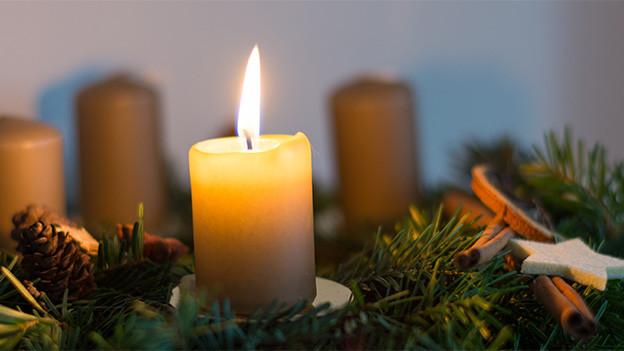 Eine brennende Kerze auf einem Adventskranz.