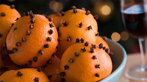 Eine Schale voller Orangen, die mit Nelken besteckt sind.
