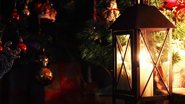 Eine Laterne vor einem weihnachtlich dekorierten Fenster.