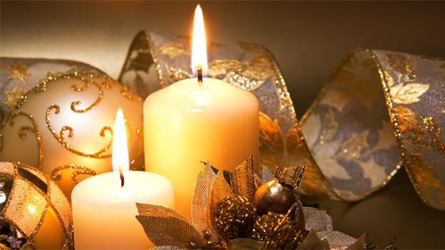 Zwei brennende Kerzen neben Weihnachtskugeln.