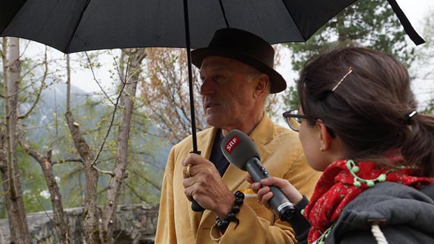 Ein Mann steht unter einem Regenschirm während ihn eine Radioreporterin interviewt.
