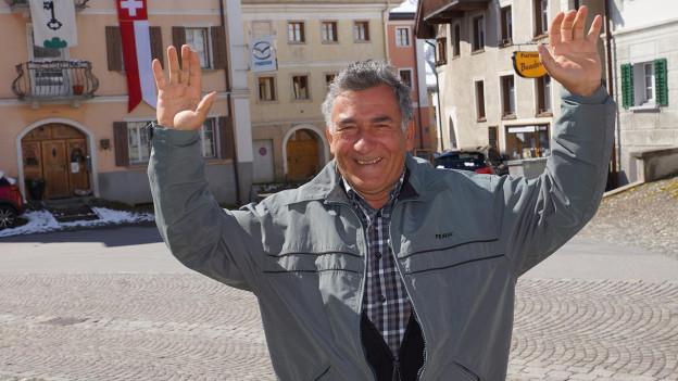 Ein Mann streckt lachend seine beiden Hände in die Höhe.