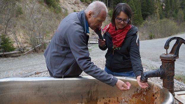 Ein Mann und eine Frau stehen vor einem alten Brunnen, der an eine Badewanne erinnert.
