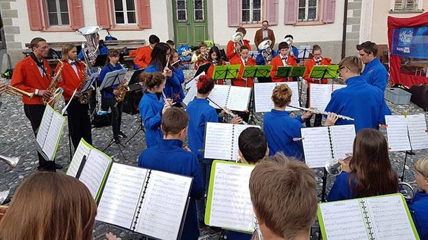 Eine Blasmusikformation mit jungen Musikantinnen und Musikanten auf einem Dorfplatz.