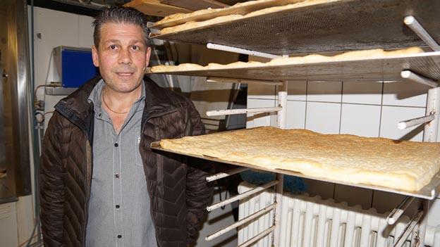 Ein Mann mit dunkler Jacke steht neben einem Regal mit Kuchenblechen.