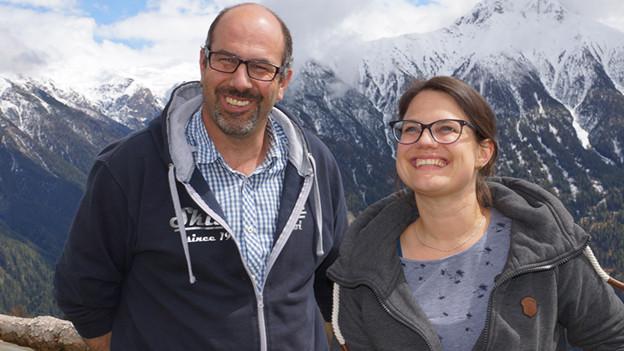 Ein Mann und eine Frau stehen lachend hoch oben in den Bergen.