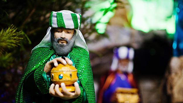 Eine Figur, die einen König darstellt, der ein wertvolles Geschenk trägt.
