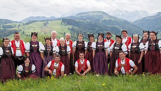 Jodelchor mit Viilett gekleideten Damen und Herren in rot-weiss.