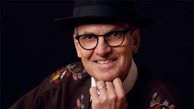 Ein Mann mit schwarzem Hut und Sennenhemd.
