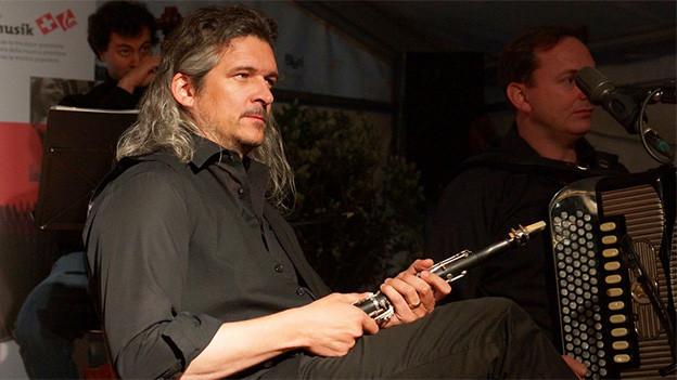 Ein Mann mit schwarzem Hemd und schulterlangen Haaren sitzt mit einer Klarinette auf einer Bühne.