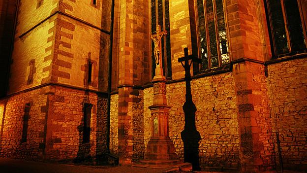 Jesus Christus am Kreuz vor einer Kirche im Abendlicht.