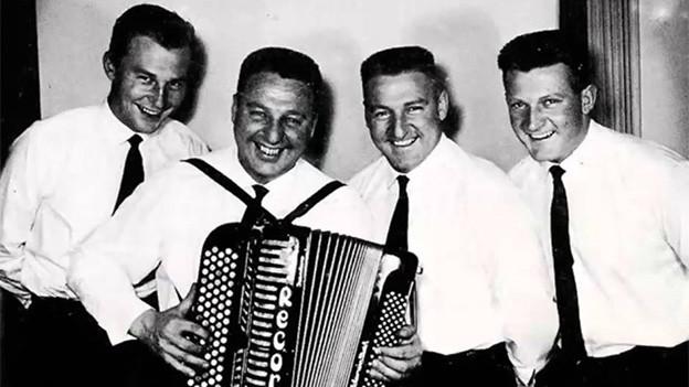 Schwarz-Weiss-Fotografie von vier Musikanten in weissen Hemden.