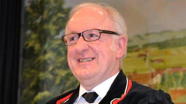 Ein älterer Mann mit Brille und Sennenhemd.