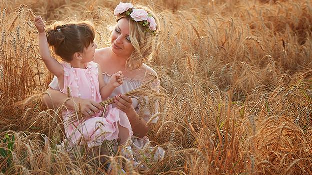Eine Mutter sitzt mit ihrer kleinen Tochter in einem Kornfeld.