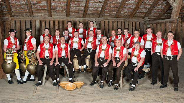 Gruppenfoto von Männern in Appenzeller Tracht in einer grossen Scheune.