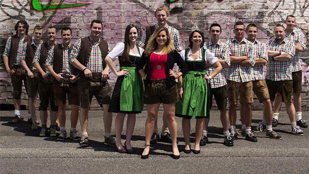 Junge Frauen und Männer vor einer Steinmauer.